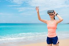 Smiling beauty girl jogger wearing VR technology. Standing on beach and using hand touching simulation playing 3D video game relaxing Stock Images