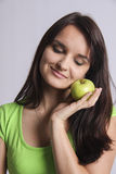 Smiling beauty holding green apple near her cheeck Stock Photo
