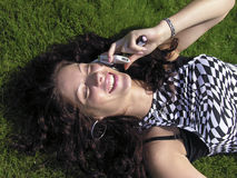 Smiling beauty and phone. Girl talking on a mobile while laying in the grass Royalty Free Stock Images