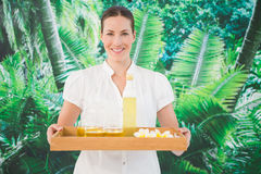 Smiling beauty therapist holding tray of beauty treatments Stock Image