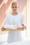 Smiling beauty therapist holding tray of beauty treatments Stock Photography