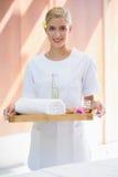 Smiling beauty therapist holding tray of beauty treatments Stock Photography