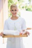 Smiling beauty therapist holding tray of beauty treatments Royalty Free Stock Photos