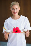 Smiling beauty therapist holding tray of treatments Royalty Free Stock Images