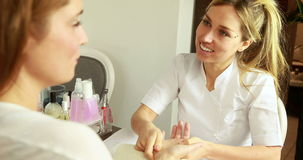 Smiling beauty therapist massaging customers hands stock video footage