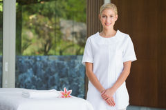 Smiling beauty therapist standing beside massage towel Stock Photos