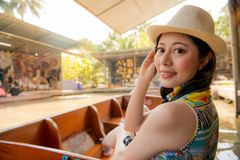 Travel girl turn around to looking at camera. Smiling beauty travel girl turn around to looking at camera when she travel in Damnoen Saduak floating market Royalty Free Stock Photography