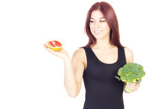 Smiling beauty woman looking at grapefruit and holding broccoli. Woman sitting on a diet. Vegan food. Stock Photos