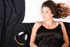 Smiling in bed with headsets Royalty Free Stock Photos
