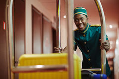 Smiling Bellboy Carrying Luggage in Cart Royalty Free Stock Photo