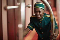 Smiling Bellboy Pushing Luggage Cart in Hotel Hallway Stock Image