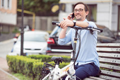 Smiling bespectacled man speaking on cellphone. So happy today. Handsome bespectacled happy man sitting on the bench and smiling while speaking on cellphone Royalty Free Stock Photo