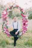 Smiling best man in the dark suit with black suspenders is sitting on the wedding peonies arch located in the park. Royalty Free Stock Images