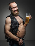 Smiling biker with beer belly. Stock Photo