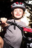 Smiling Biker at Dusk. An excited smiling preteen boy at dusk with bike helmet on bike. Shallow depth of field Stock Images