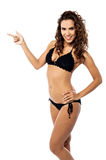 Smiling bikini woman pointing her finger Royalty Free Stock Image