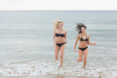 Smiling bikini women running in water at beach Stock Photos