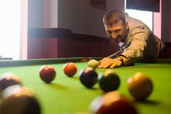 Playing in billiard club. The smiling billiard player is playing billiard or snooker in the billiard club, cue sport concept royalty free stock photos
