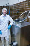 Smiling biologist leaning against storage tank. In the factory Stock Photography