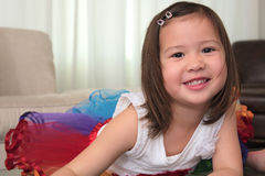 Smiling biracial female asian child lying on stomach smiling Royalty Free Stock Photos