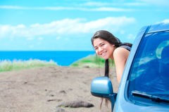 Smiling biracial teen girl leaning out car door by ocean. Smiling biracial teen girl leaning out car window on sunny day at  beach with blue Hawaiian ocean in Royalty Free Stock Image