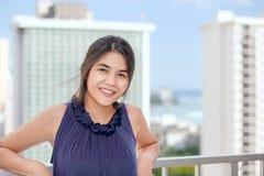 Smiling biracial teen girl on outdoor highrise patio, ocean  bac Royalty Free Stock Photos