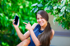 Smiling biracial teen girl pointing to cellphone in hand. Beautiful biracial teen girl holding her cellphone in hand and pointing to it, smiling Royalty Free Stock Photo