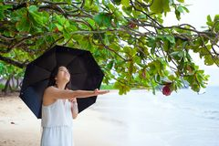 Young woman on Hawaiian beach holding umbrella in rain Royalty Free Stock Photo