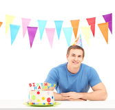 Smiling birthday guy with a party hat and a cake Royalty Free Stock Photos