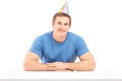 A smiling birthday guy with a party hat posing Royalty Free Stock Photo