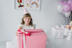 smiling birthday kid in cone sitting at table with huge gift stock photo