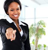Smiling black business woman pointing. On camera in office royalty free stock photo