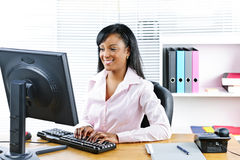 Smiling black businesswoman at desk Stock Photo