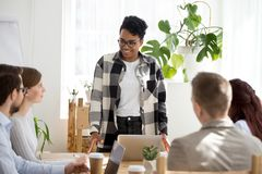 Smiling black businesswoman lead casual office meeting. Smiling black businesswoman standing lead casual meeting with colleagues, satisfied female African stock image