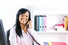Smiling black businesswoman on phone at desk Royalty Free Stock Photo