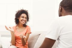 Smiling black couple drinking coffee on sofa at home. Happy african-american couple having rest at cozy home and chatting. Family leisure, lazy weekend and Stock Photos