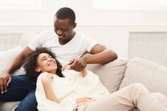 Smiling black couple having rest on sofa at home. Happy african-american couple having rest at cozy home. Family leisure, lazy weekend and relaxation concept Stock Image