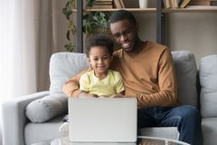 African father and little son watching cartoons on laptop. Smiling black dad hug little son sitting on sofa in living room at home spends time together watching royalty free stock photos