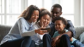 Smiling black family relax together watching cartoons on smartphone. Happy young mom hold smartphone watch funny cartoons with mixed race family, relax together stock photo
