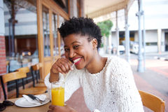 Smiling black girl drinking orange juice at outdoor cafe Stock Photos
