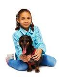 Smiling black girl hugging friendly dachhund Stock Photo
