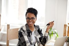 Smiling black girl laugh working at laptop in office. Smiling African American girl wearing glasses holding smartphone looking to side while working at laptop in stock photography