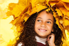 Smiling black girl wearing maple leaves crown. Beauty portrait of little black girl smiling with wreath made of orange autumn leaves Royalty Free Stock Photo