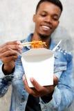 Smiling black guy eating noodles with chopsticks Stock Images