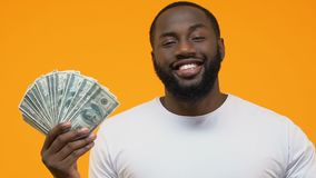 Smiling black guy pointing at dollar banknotes in hand, government payment stock video footage