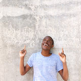 Smiling black guy pointing fingers up Stock Images