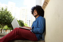 Smiling black guy sitting outside with laptop Royalty Free Stock Images