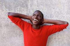 Smiling black guy standing with hands behind head Stock Photography