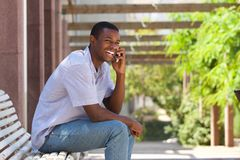 Smiling black guy talking on mobile phone outside Royalty Free Stock Image
