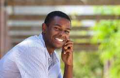 Smiling black guy using mobile phone outside Royalty Free Stock Photos